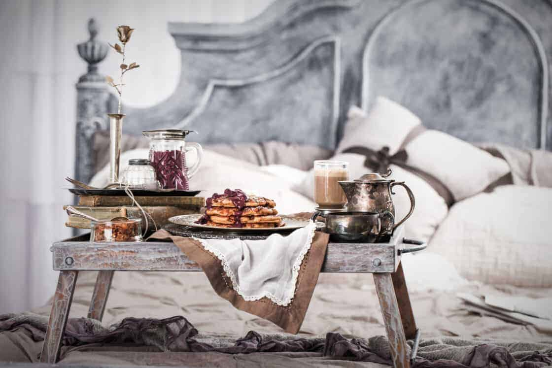 breakfast in bed with pancakes, maple coffee and blueberry syrup in a gray and white bedroom on wooden tray