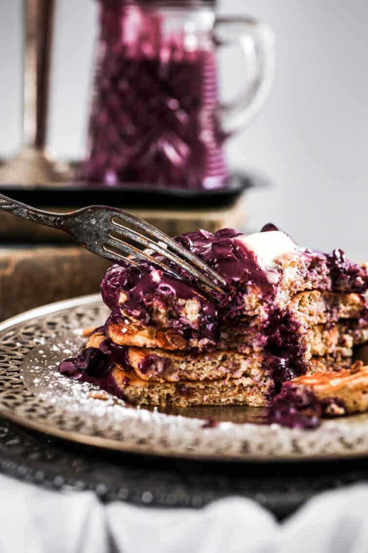 fork slicing into stack of pancakes with blueberry syrup