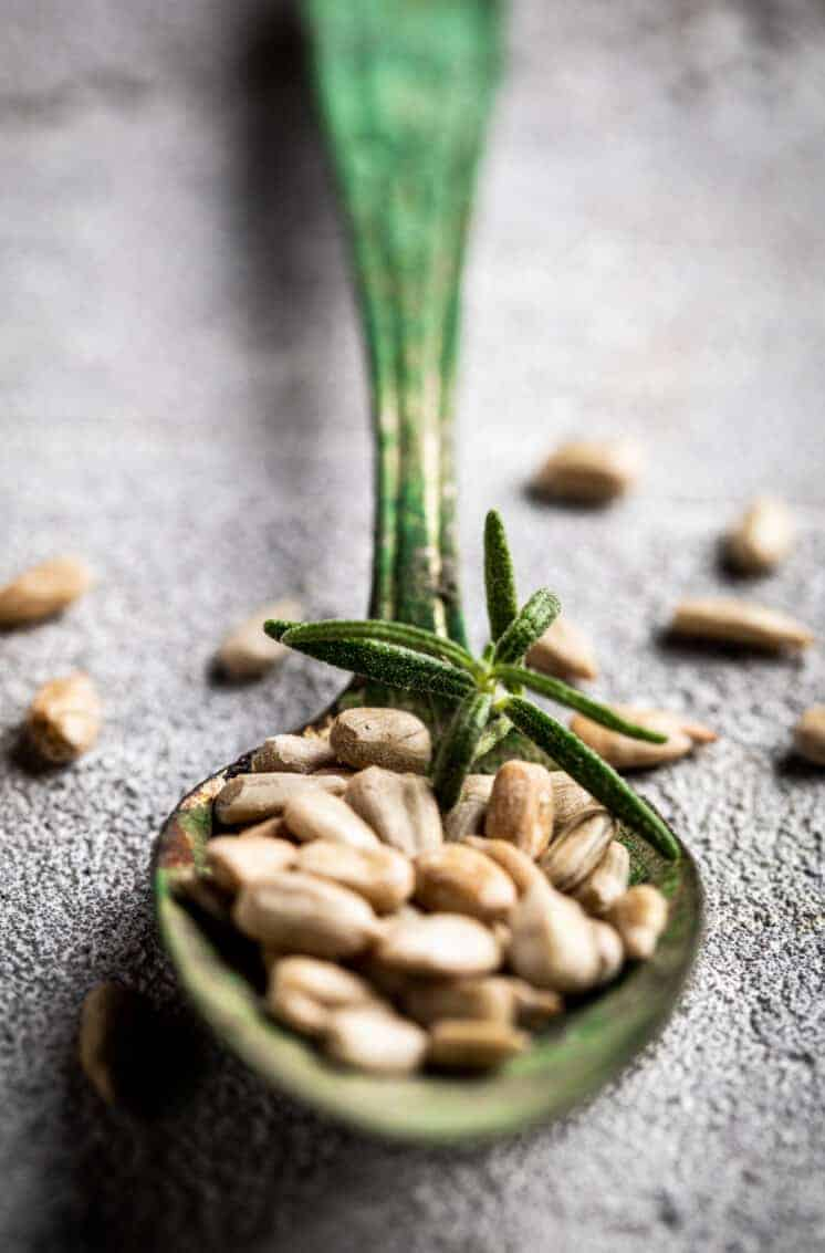 rustic green spoon with rosemary and sunflower seeds on gray surface