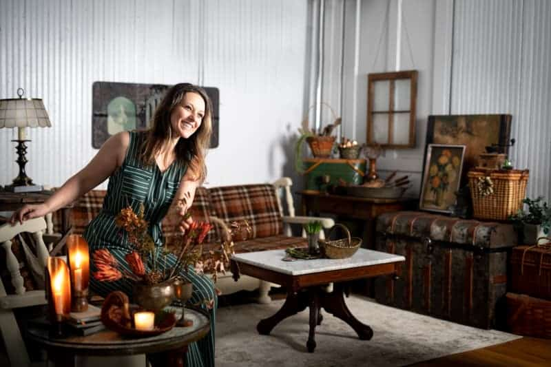 Smiling female food photographer in her studio space filled with picturesque antique props and furniture.