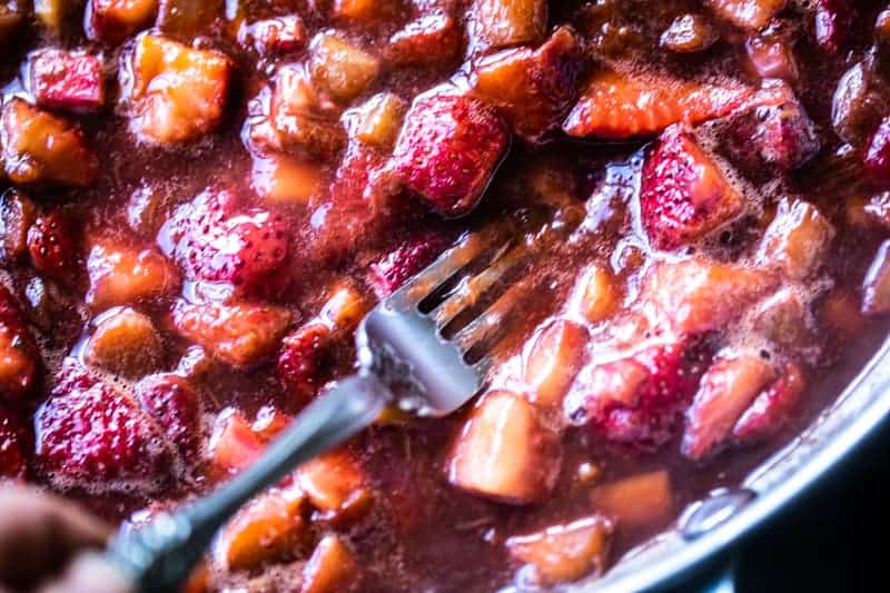 Closeup of cooked down strawberries and rhubarb with a fork mashing larger pieces.