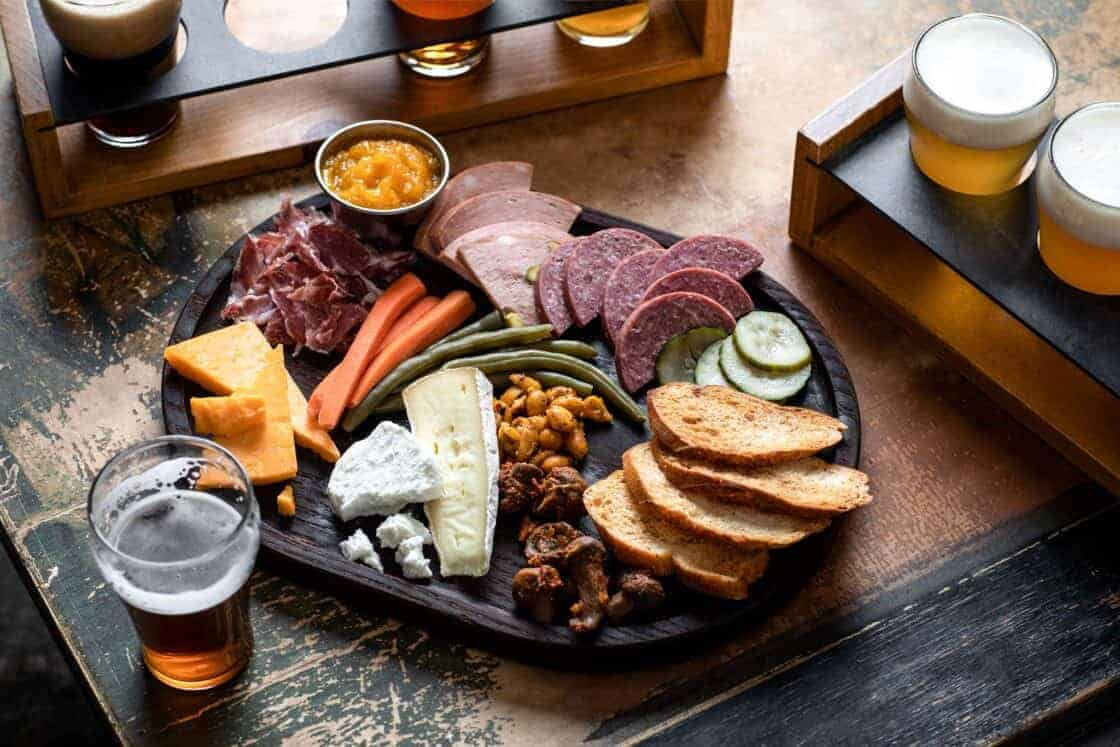 charcuterie plate with beers in restaurant setting