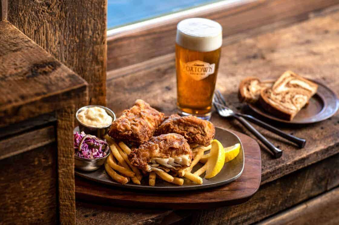 plate of a Wisconsin fish fry with a beer in restaurant setting