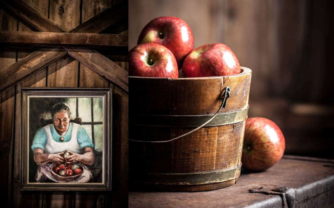 A wooden bucket of apples and a woman peeling apples
