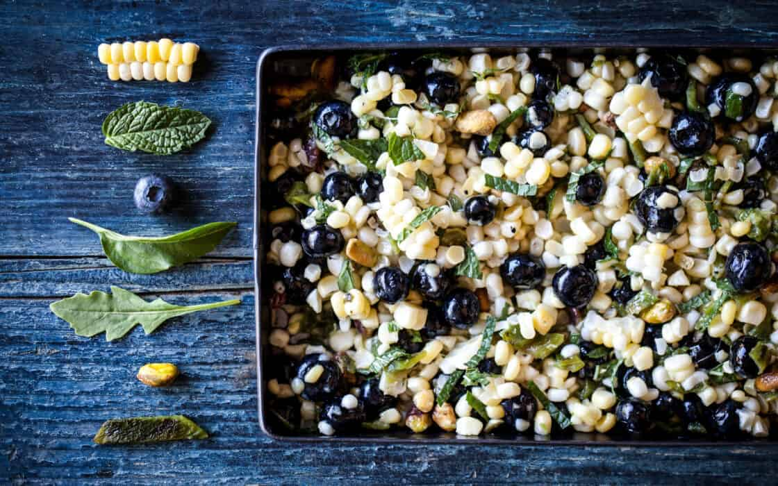 Tray of blueberry corn salsa with individual ingredient flat lay