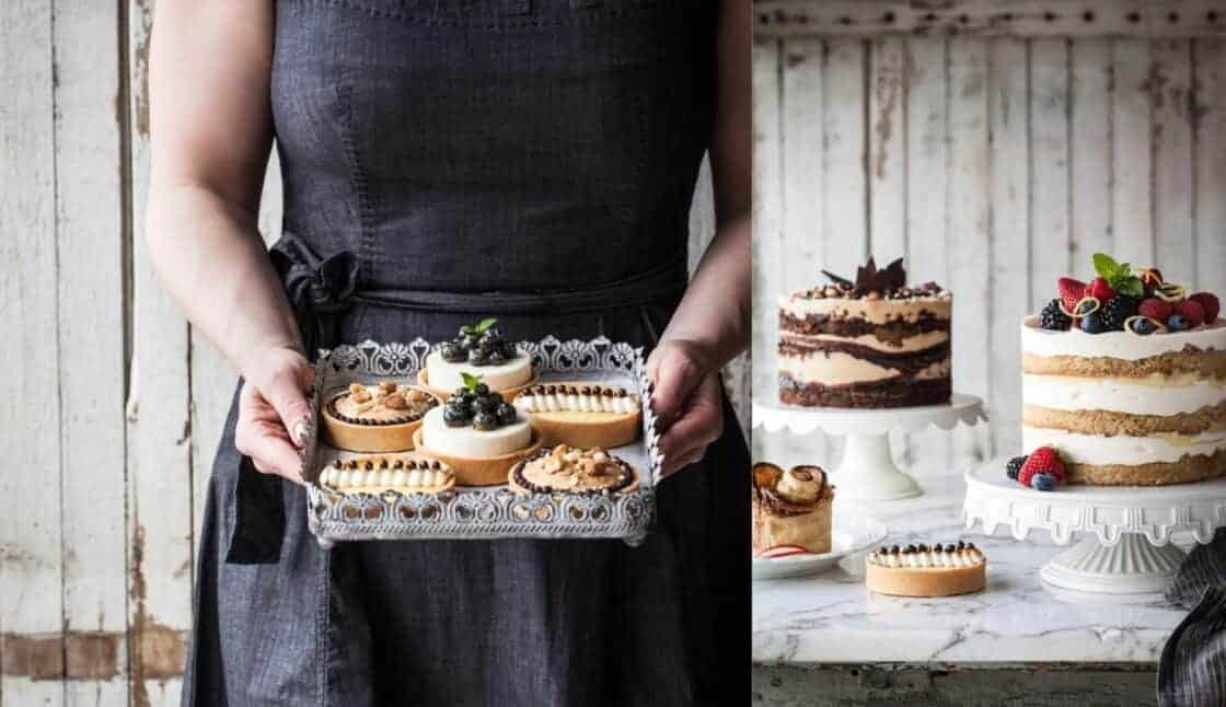 woman holding a metal tray of tarts and layered cakes on cake plates