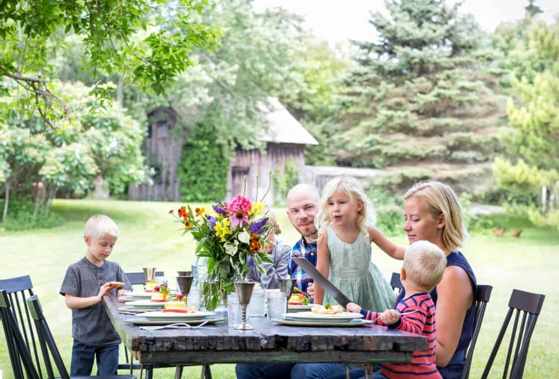 family sitting at a big table on a farm with flowers and place settings