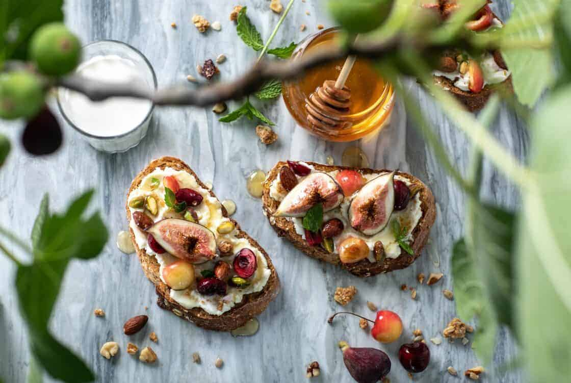 overhead shot with out of focus foreground and fig toast and honey on wooden surface
