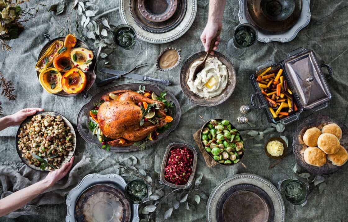 overhead shot of a complete Thanksgiving dinner on a moody surface