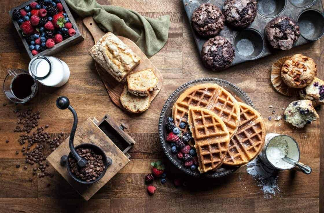 overhead photo of wooden breakfast table with waffles, coffee beans, muffins, and berries