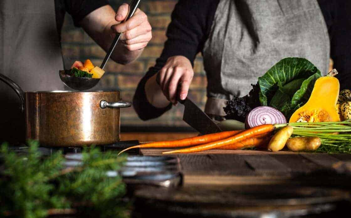 Two people cooking with pot, ladle, and carrots