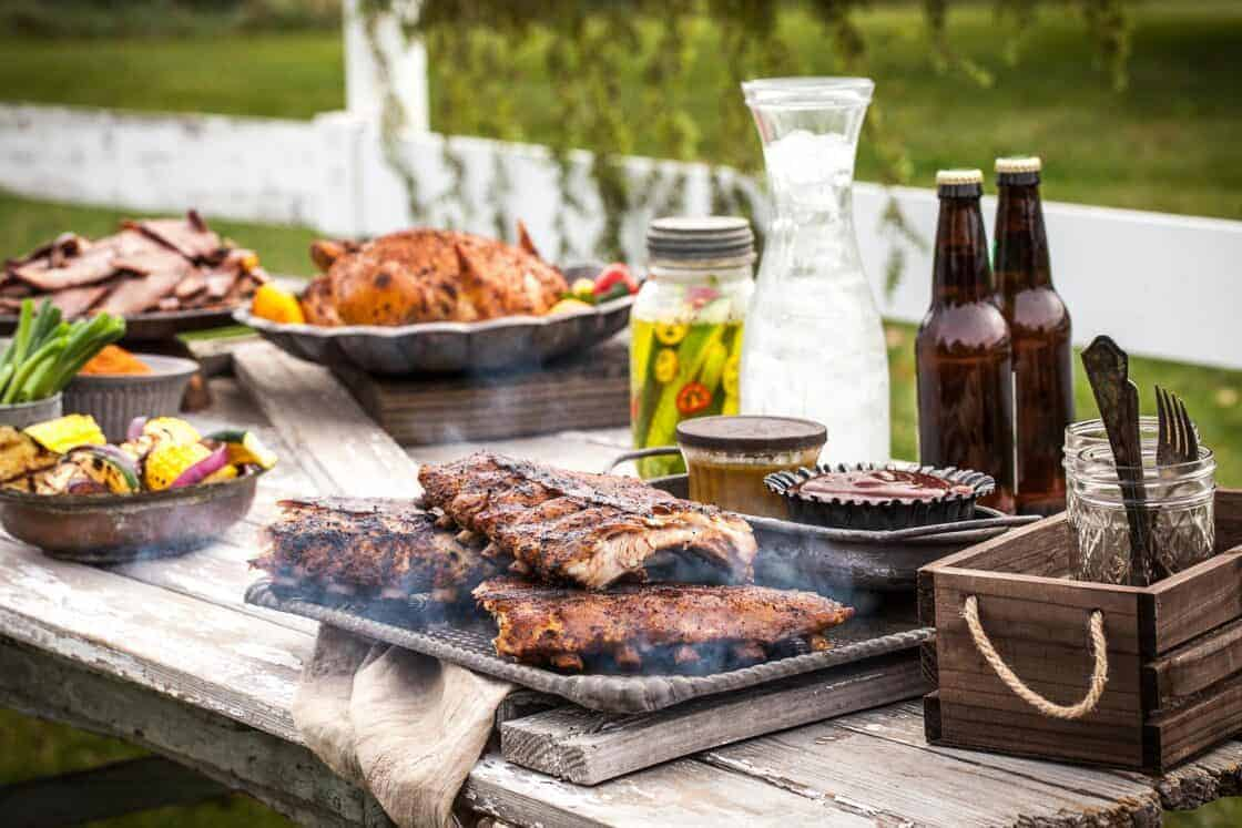outdoor grilling spread with ribs, chicken, and sides