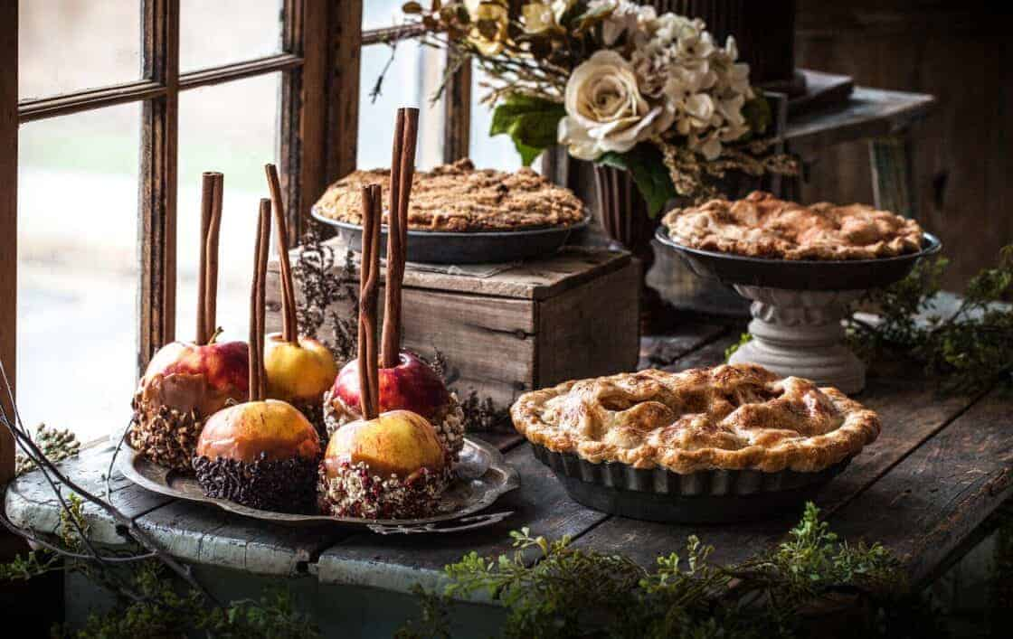 Table setting by a big window with pies and caramel apples