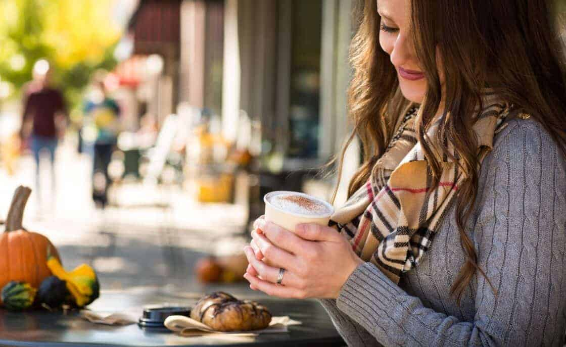 woman sitting outside coffee shop with coffee
