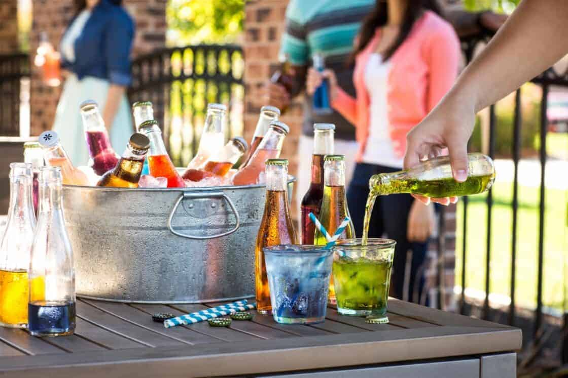 Metal bucket of colorful glass soda bottles at summer party with person pouring soda