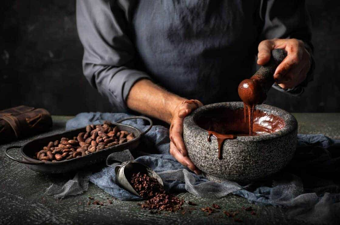 Stirring up melted chocolate in a stone bowl with a pestle