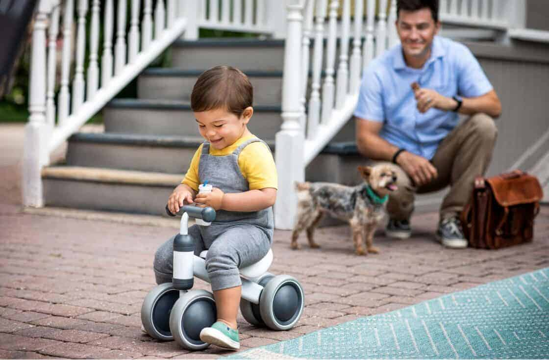 Son riding a little bike with dad and puppy looking on
