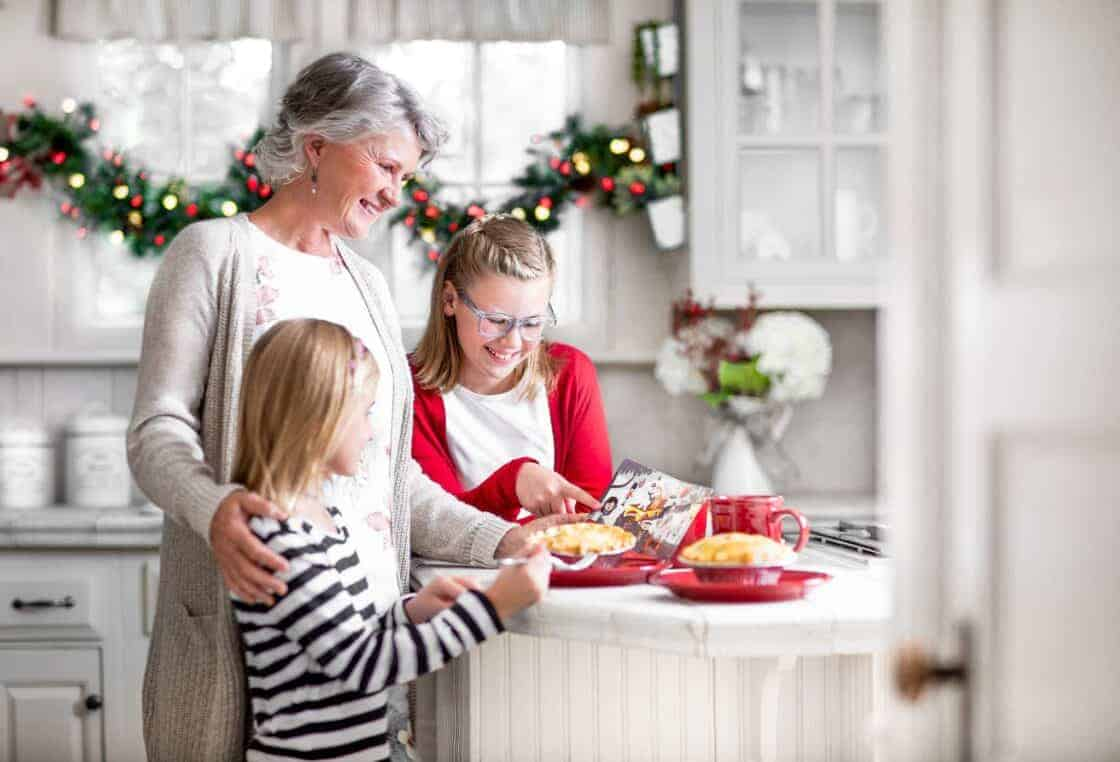 Three generations of women in a kitchen decorated for Christmas