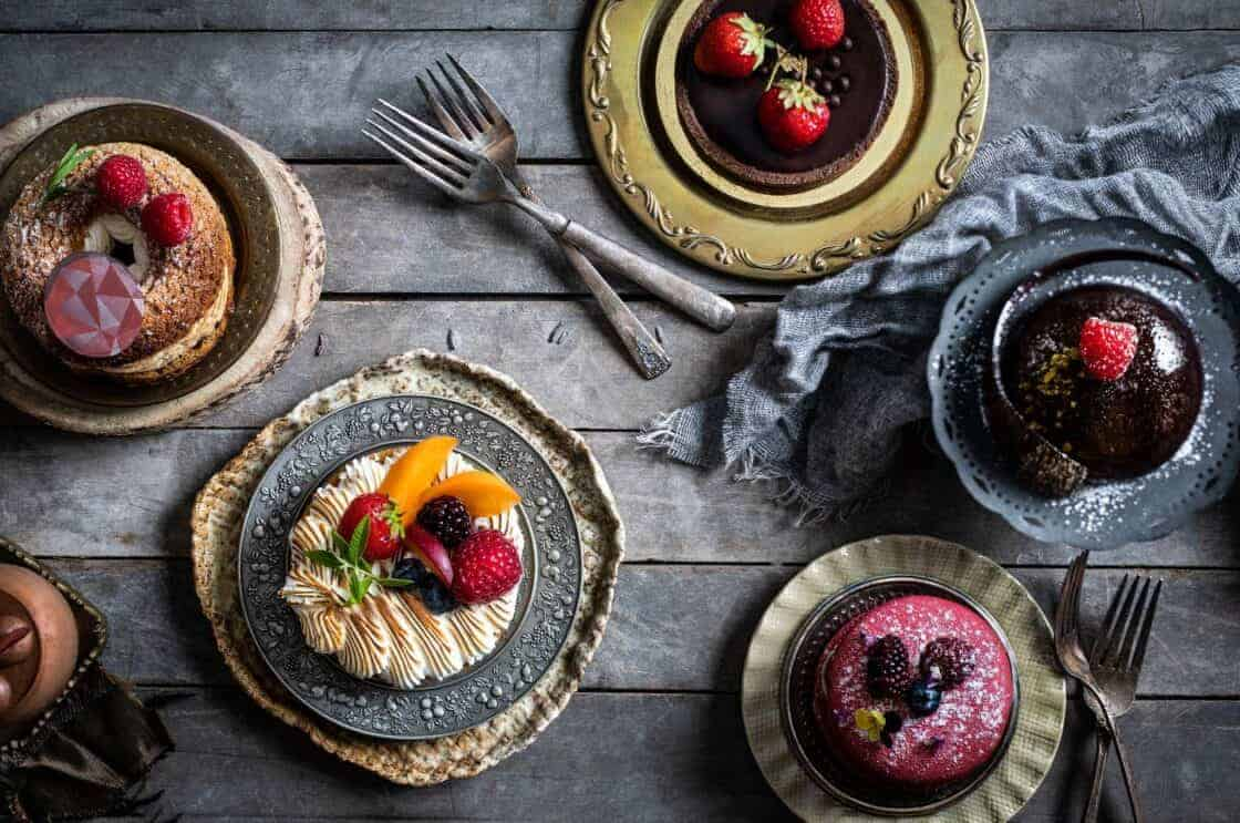 overhead shot of desserts with berries on a dark surface
