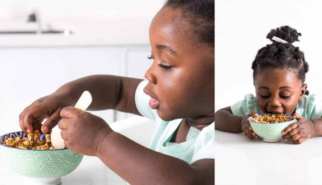 little girl eating cereal in a white kitchen