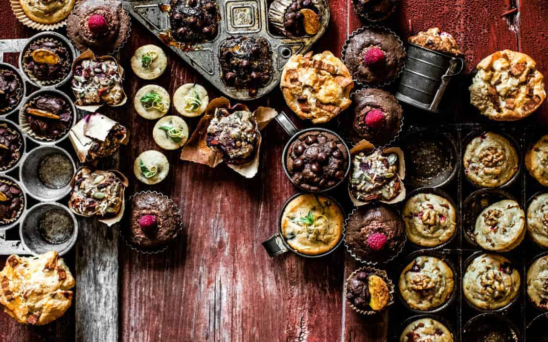 overhead shot of many types of muffins in antique tins on red barn wood