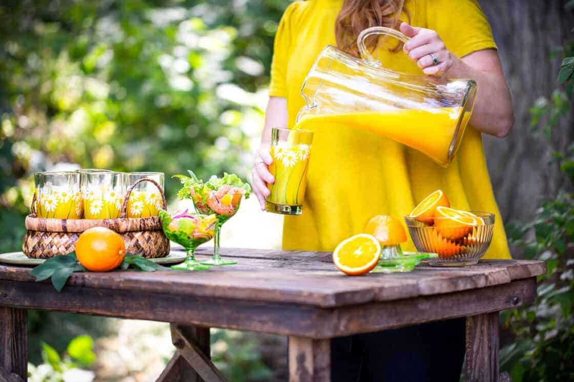 Woman pouring orange juice outside at a table