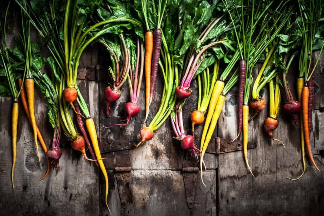 a beautiful spread of colorful root vegetables, beets, carrots