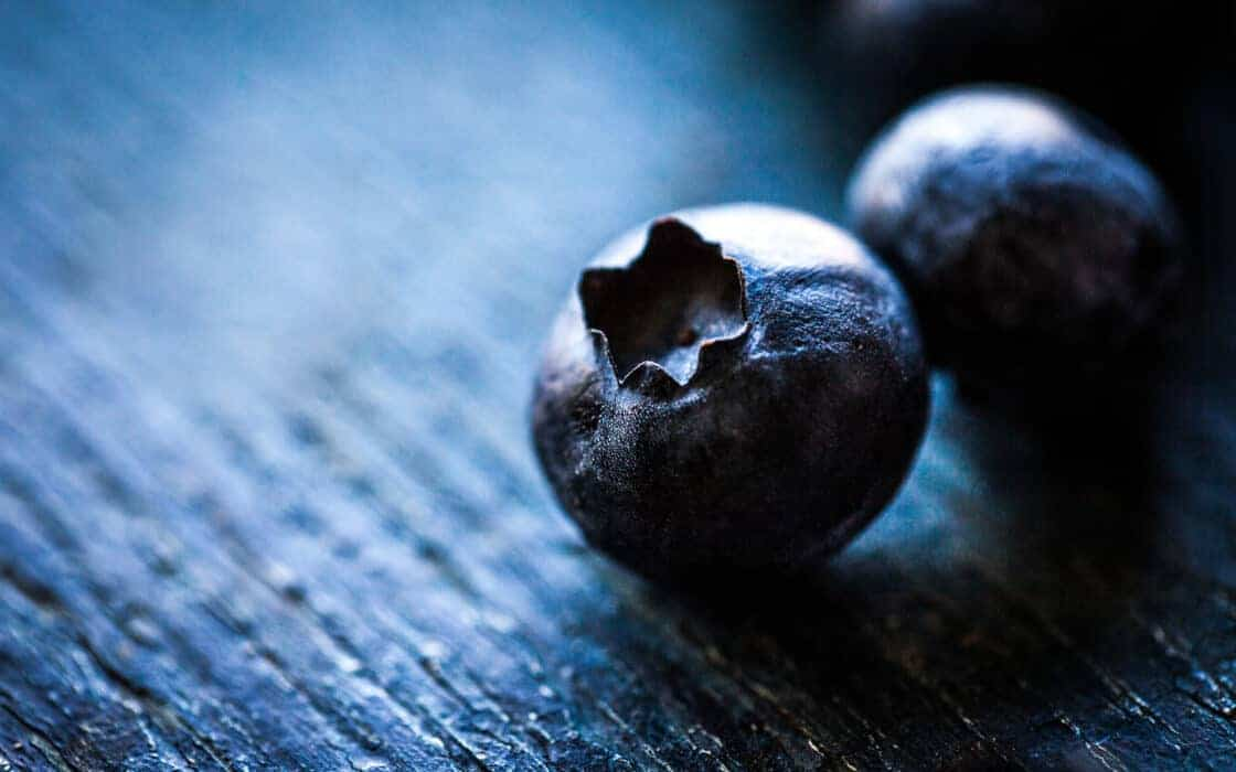 closeup of two blueberries in rustic setting