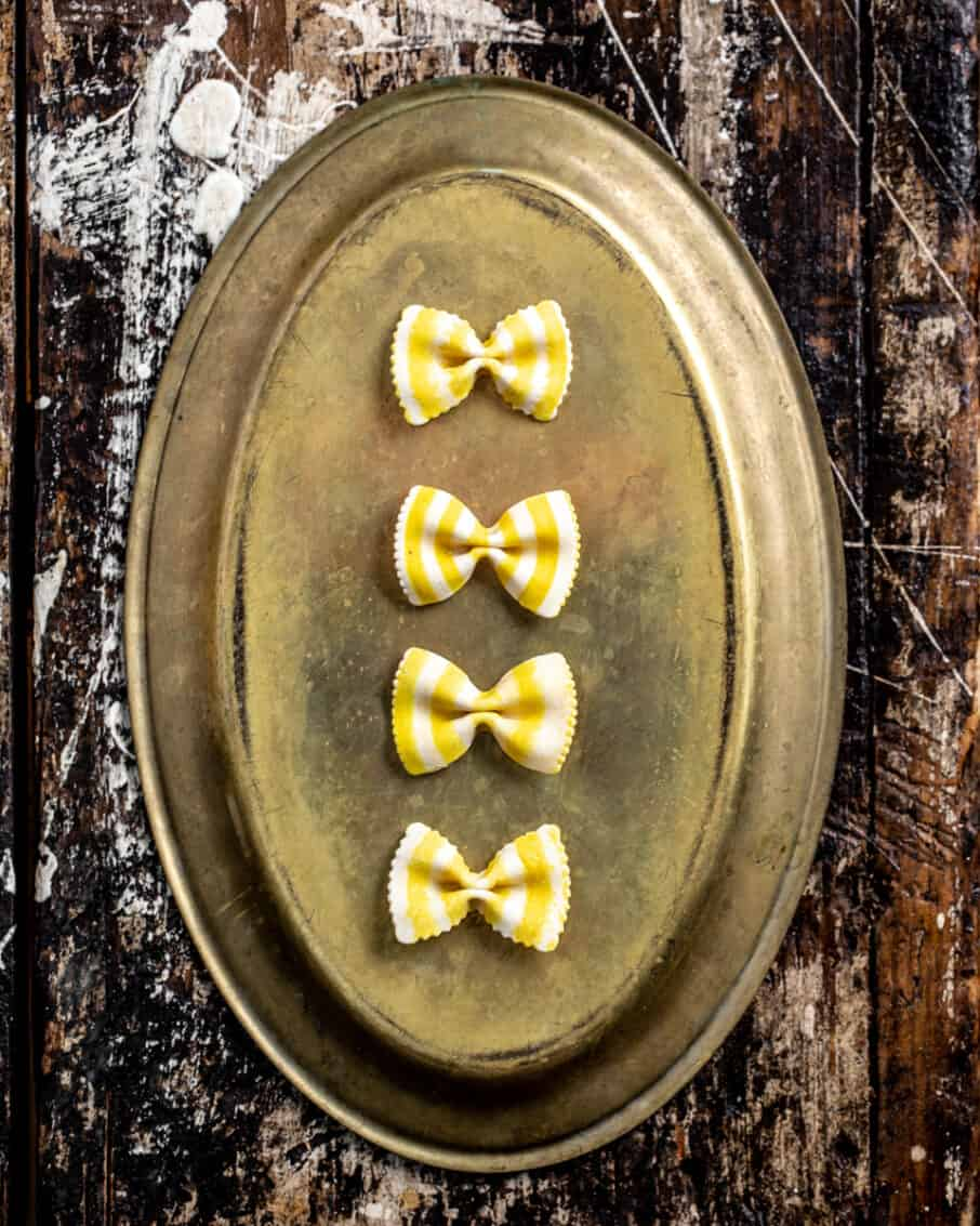 Four white and yellow striped bowtie pastas arranged on a antique platter and a rustic surface.