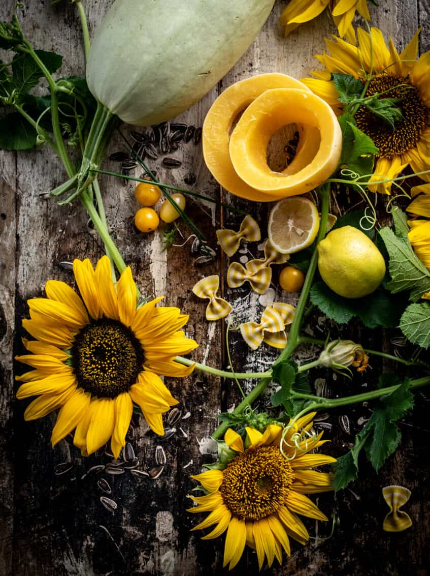 Overhead shot of artfully grouped ingredients nd fresh sunflowers. Sunflower seeds, striped bowtie pasta, cut lemons and squash, and cherry tomatoes.