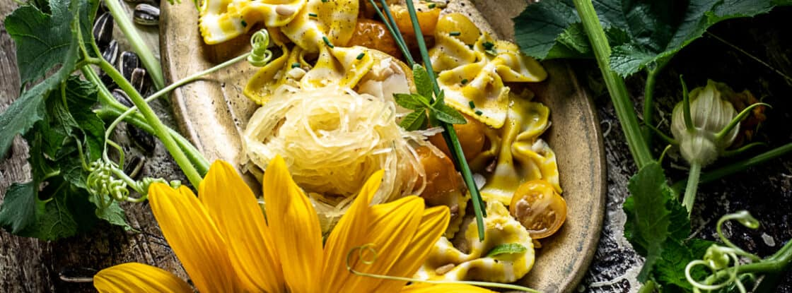 Overhead shot of sunflower lemon pasta in rustic dish surrounded by fresh sunflowers.