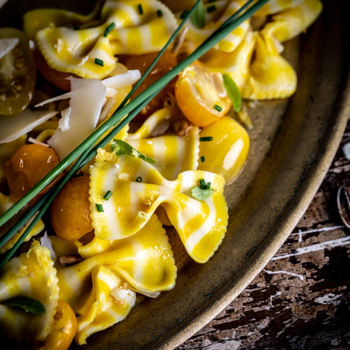 Close up of sunflower bowtie pasta dish on a vintage platter with fresh herbs.