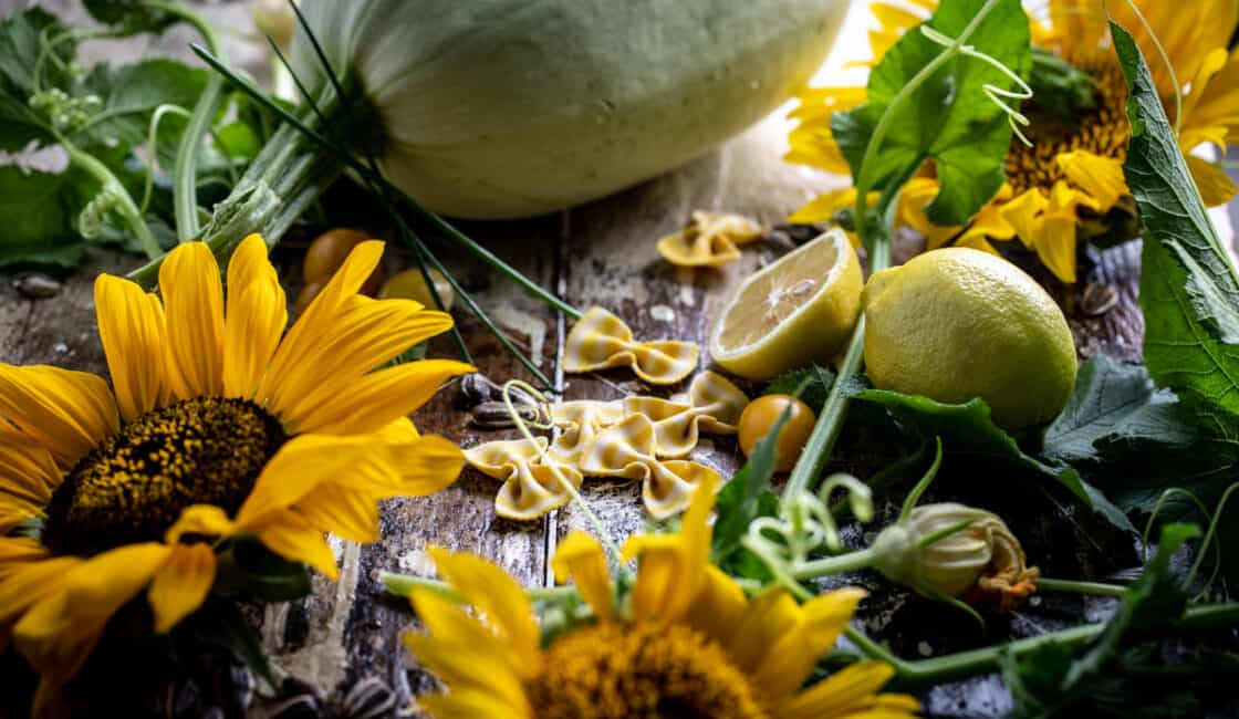 Fresh recipe ingredients gathered on a rustic surface with large sunflowers and a spaghetti squash.