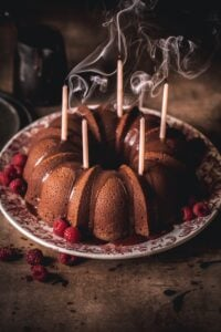 Chocolate bunt cake with blown out candles and swirling smoke.