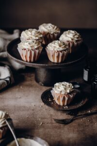 White frosted cupcakes on black cake stand in moody setting.