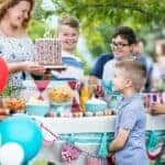 A woman bring a sprinkled birthday cake to a picnic table with kids and balloons