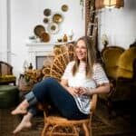 Jena Carlin photographer sitting sideways in a wicker chair and smiling